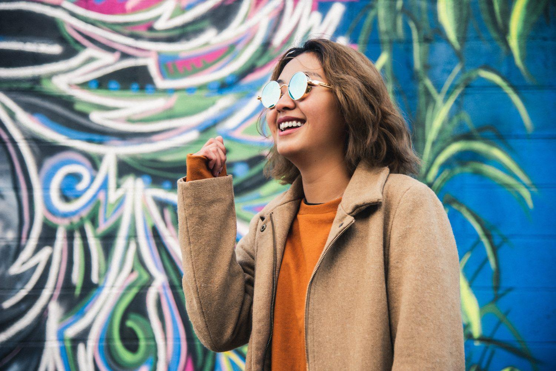 woman smiling by graffitti