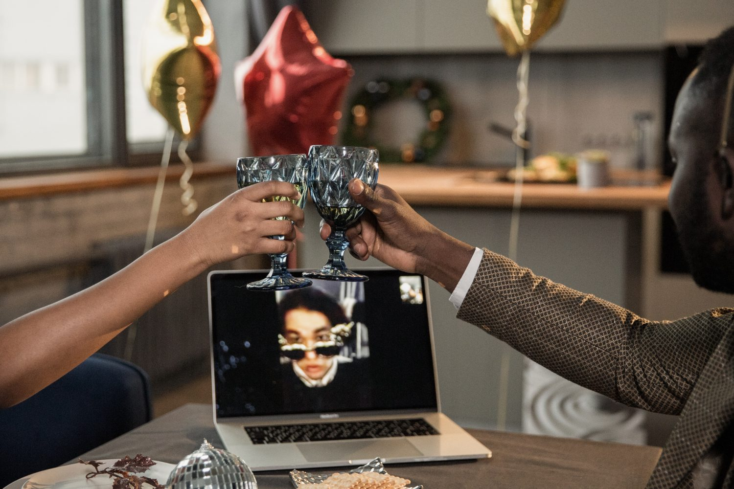 People toasting with cups in front of a computer screen